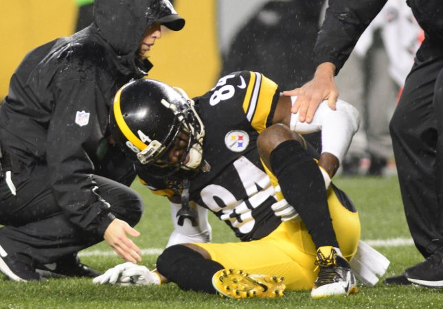 9e75a938d Pittsburgh Steelers receiver Antonio Brown reaches for his leg in pain and  leaves the game in the second quarter in Sunday s home loss to the New  England ...