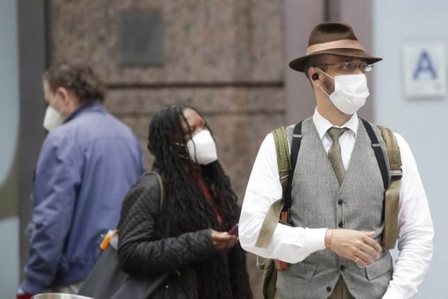 Pedestrians wear face masks in Times Square in New York City on Wednesday. Photo by John Angelillo/UPI