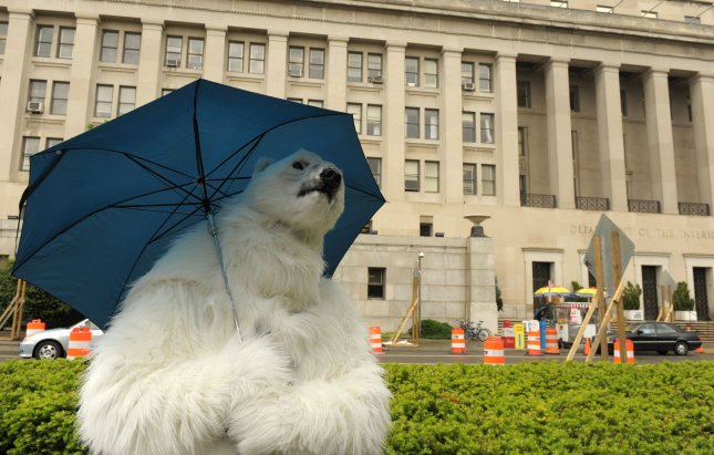 A man dressed as a polar bear, carrying an umbrella, stands in front of the Interior Department in Washington on May 7, 2009. The polar bear joined school children delivering petitions to ask Secretary of the Interior Ken Salazar to rescind Bush-administration-era regulations that weaken protections for the bears. (UPI Photo/Roger L. Wollenberg)