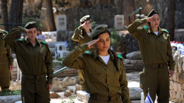 Israeli soldiers salute after decorating graves of fallen soldiers with national flags with black ribbons for Remembrance Day at the Mt. Herzl Military Cemetery in Jerusalem, Israel, April 14, 2013. Israel's Remembrance Day for fallen soldiers begins at sunset with a one minute siren. UPI/Debbie Hill