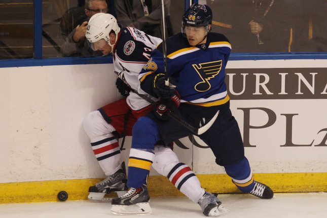 Scott Hartnell of the Columbus Blue Jackets is shoved into the boards by the St. Louis Blues' Ian Cole. The Blue Jackets bought out Hartnell's contract Thursday. Photo by BIll Greenblatt/UPI