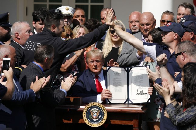 Sept. 11 responders react after President Donald Trump signed an act to permanently authorize September 11th Victim Compensation Fund bill, in the Rose Garden of the White House on Monday. Photo by Yuri Gripas/UPI