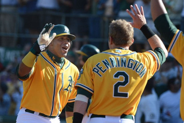 Oakland A's Yoenis Cespedes (L) celebrates with Cliff Pennington after scoring in the eighth inning against the Texas Rangers at the Coliseum in Oakland, California on October 3, 2012. The A's took the game 12-5 and the AL West. UPI/Terry Schmitt