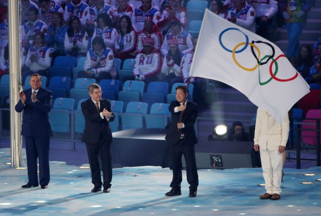 Lee Seok-rae, mayor of PyeongChang, South Korea, which will host the 2018 Winter Olympics, holds the Olympic flag at the closing ceremonies of the Games in Sochi, Russia, Feb. 23, 2014. Applauding are Sochi Mayor Anatoly Pakhmov (L) and Thomas Bach, president of the International Olympic Committee. (The IOC was founded on June 23, 1894.) File Photo by Kevin Dietsch/UPI