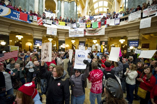 Teachers march through the rotunda at the state Capitol to protest pending budget legislation in Madison, Wisconsin on February 24, 2011. Protests continued for the 11th day as a bill slashing benefits and revoking collective bargaining rights from state workers nears passage. UPI/Brian Kersey