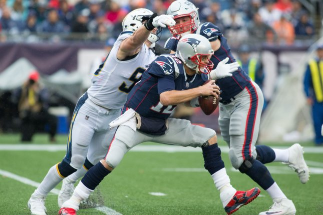 New England Patriots quarterback Tom Brady (12) dodges a sack by Los Angeles Chargers defensive end Joey Bosa (99) as Patriots offensive tackle Nate Solder (77) pushes Bosa away in the third quarter on October 29 at Gillette Stadium in Foxborough, Mass. Photo by Matthew Healey/UPI