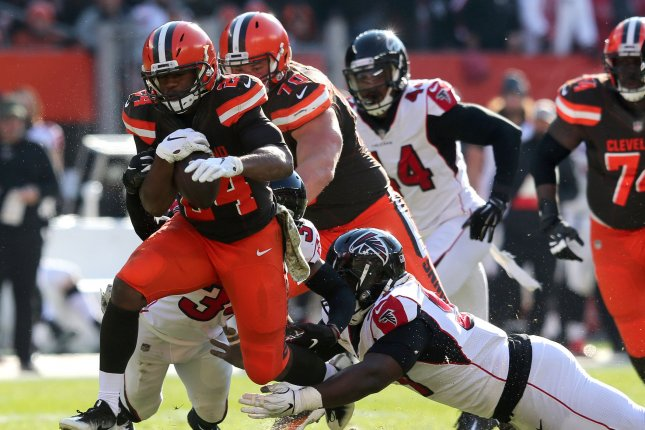 Cleveland Browns running back Nick Chubb (24) kicks up some dirt and drags Atlanta Falcons defenders Brian Poole (L) and Grady Jarrett during a run on Sunday at FirstEnergy Stadium in Cleveland, Ohio. Photo by Aaron Josefczyk/UPI