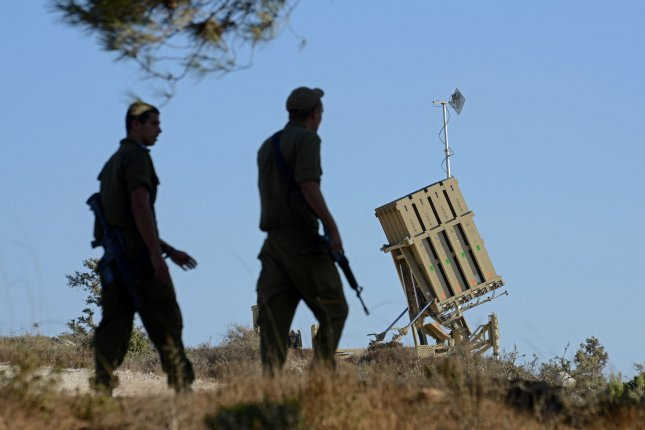 Israeli soldiers walk near an Iron Dome anti-missile defense battery on the outskirts of Jerusalem, Israel, September 9, 2013. UPI/Debbie Hill