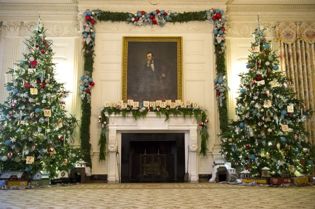 Christmas decorations in the State Dining Room at the White House include two 14-foot-tall trees and letters on the mantel, beneath Abraham Lincoln's portrait, that spell Winter Wonderland. Parts of children's toy train sets are placed beneath the trees. (This view is on Dec. 3, 2014.) UPI/Kevin Dietsch