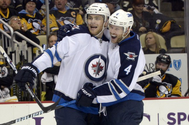 Winnipeg Jets defenseman Paul Postma (4) and Winnipeg Jets center Adam Lowry (17) celebrate a goal. File photo by Archie Carpenter/UPI