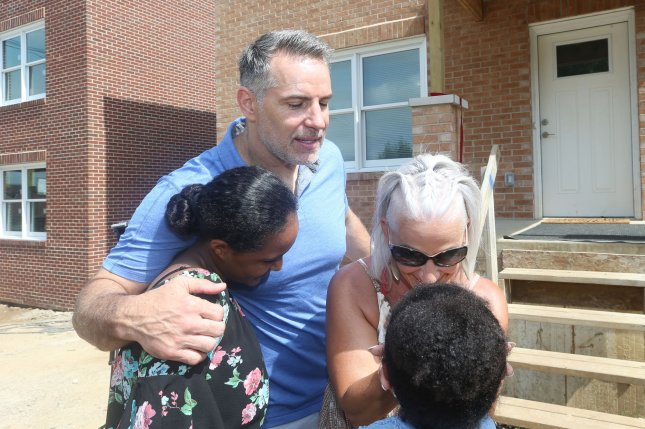 Hall of Fame quarterback Kurt Warner and wife Brenda embrace a family that has been presented a new home in St. Louis on Saturday. Photo by Bill Greenblatt/UPI
