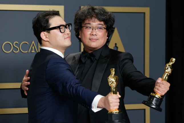 Han Jin-won (L) and Bong Joon-ho, winner of best original screenplay, best director and best picture for Parasite, appear backstage with their Oscars in Los Angeles on Sunday night.  Photo by John Angelillo/UPI
