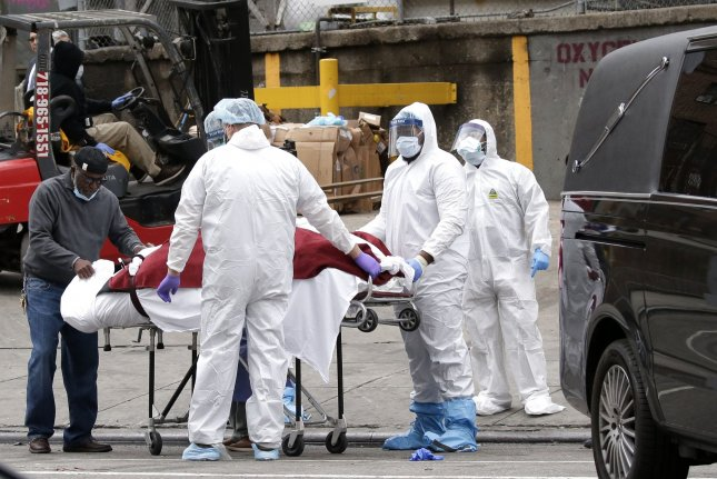 A body wrapped in red fabric is rolled to a hearse, handled by medical workers wearing  masks, equipment and garments as protection from COVID-19 contamination at Brooklyn Hospital Center in New York City on Tuesday.  Photo by John Angelillo/UPI