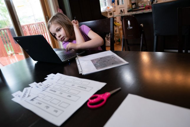 First-grader Violet Kimbrough works on a lesson via distance learning as a result of the COVID-19 pandemic, in Silver Spring, Md., on April 30. File Photo by Kevin Dietsch/UPI