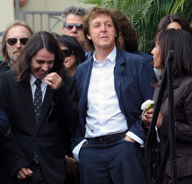Paul McCartney (C), mingles with his former Beatles bandmate George Harrison's son Dhani during a posthumous Hollywood Walk of Fame star dedication for Harrison in Los Angeles on April 14, 2009. At right is Harrison's widow Olivia. (UPI Photo/Jim Ruymen)