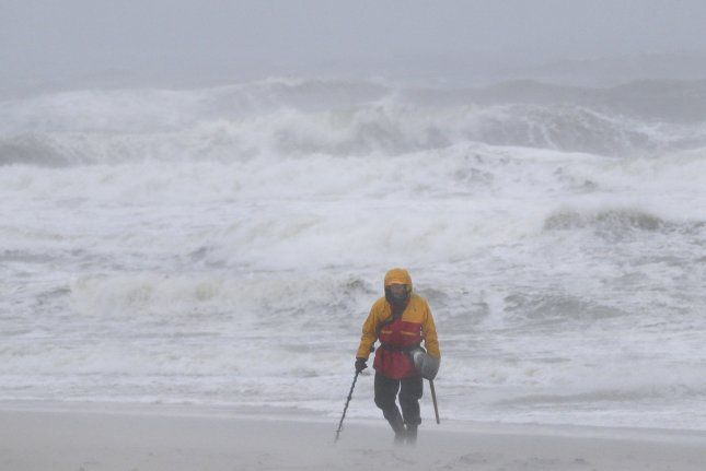 High waves and rough waters hit the shore line as a man walks on the beach with a metal detector when rain and wind arrives on the east coast of the United States on October 2, 2015 in Seaside Heights, NJ. The flooding scenario will develop Friday night and through the weekend as flash flood watches extend from Atlanta to near New York City. Though the East Coast braced for Hurricane Joaquin, the rainy weather is part of a different weather system. Photo by John Angelillo/UPI