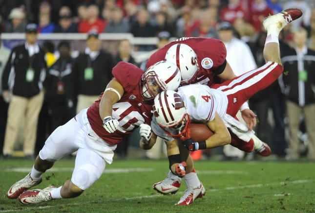 Stanford Cardinal linebacker Joe Hemschoot stops Wisconsin Badgers wide receiver Jared Abbrederis on a kickoff return in the 2013 Rose Bowl. Kickoffs, with their high rate of severe injuries from high-speed tackles, soon may be history in college football. File photo by Lori Shepler/UPI