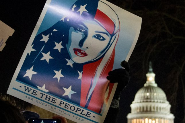 A protester holds up a sign in front of the Capitol building at a candlelight vigil in front of the U.S. Supreme Court on Monday to call on U.S. President Trump to reverse his administration's recent anti-refugee and anti-immigrant executive orders that bar for 90 days people traveling from Iraq, Iran, Sudan Syria, Yemen, Libya and Somalia to the United States. Muslim advocacy group CAIR sued the Trump administration Monday, saying his order violated the Establishment Clause of the First Amendment. Photo by Erin Schaff/UPI