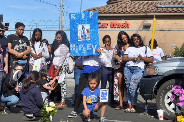 Fans gather around a makeshift memorial for Ermias Ashgedom, better known as rapper Nipsey Hussle, in the parking lot of his clothing store in the Crenshaw area of Los Angeles on Sunday. Photo by Jim Ruymen/UPI