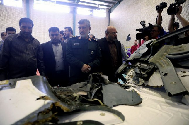 The head of the Revolutionary Guard's aerospace division Gen. Amir Ali Hajizadeh looks at the wreckage of U.S. drone RQ-4A, which is displayed by Iran's Revolutionary guard in Tehran, Iran on Friday. Photo by ISNA Borna Qasemi/UPI