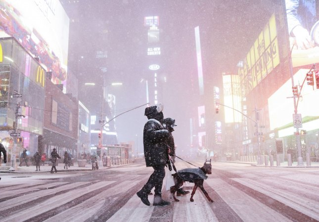 A dog is walked across 7th Avenue while heavy snow continues to fall in Times Square in New York City on Wednesday. A winter storm nor'easter is set to possibly dump more than a foot of snow in parts of New York State and the Northeast. Photo by John Angelillo/UPI