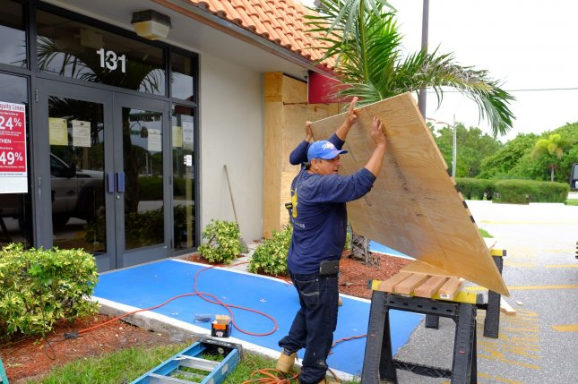 A construction crew is boarding up the glass doors at a BB&T bank branch in Lantana, Fla., on Thursday, in anticipation of Hurricane Matthew, a Category 4 storm scheduled to make landfall Thursday night. The hurricane's potential devastation could serve as the October surprise in the 2016 election, testing how Hillary Clinton and Donald Trump respond to a disaster. Photo by Gary I Rothstein/UPI...