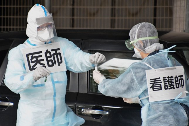 A medical worker collects a sample for polymerase chain reaction tests for the coronavirus disease on May 10 during a simulation for drive-through at the Kashima soccer Stadium in Ibaraki-Prefecture, Japan. Photo by Keizo Mori/UPI