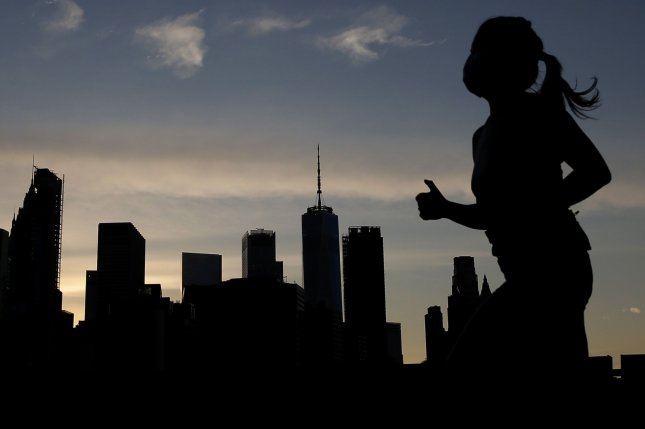 A woman wearing a mask jogs in New York City's Brooklyn Bridge Park on June 25, with One World Trade Center and the Manhattan Skyline in the background at sunset. Photo by John Angelillo/UPI