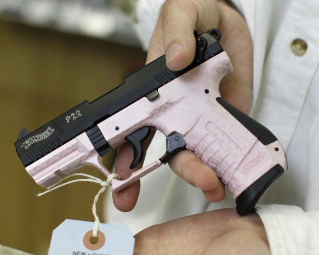 Greg Tropino Jr. displays a pink-colored handgun at G. A. T. Guns in Dundee, Illinois on June 28, 2010. The pink-colored weapons are designed to appeal more to women. The Supreme Court held Monday that Americans have the right to own a gun for self-defense anywhere they live, striking down Chicago's nearly 30-year-old handgun ban. UPI/Brian Kersey