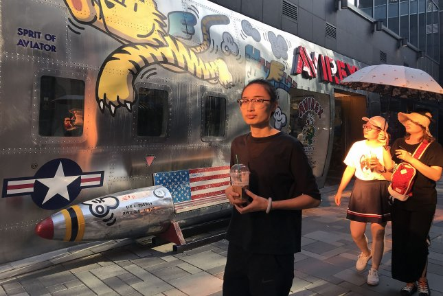 Pedestrians walk by a store specializing in American fashion, and displaying a bench shaped as a U.S. missile, in Beijing, China, on August 14. Photo by Stephen Shaver/UPI