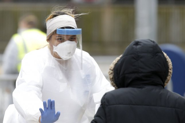 A healthcare workers wears an N95 respirator as she consults with a patient who arrives to be tested for coronavirus in Yonkers, N.Y., on April 17. Twenty attorneys general urged 3M to take steps to prevent price gouging on the respirators. File Photo by John Angelillo/UPI