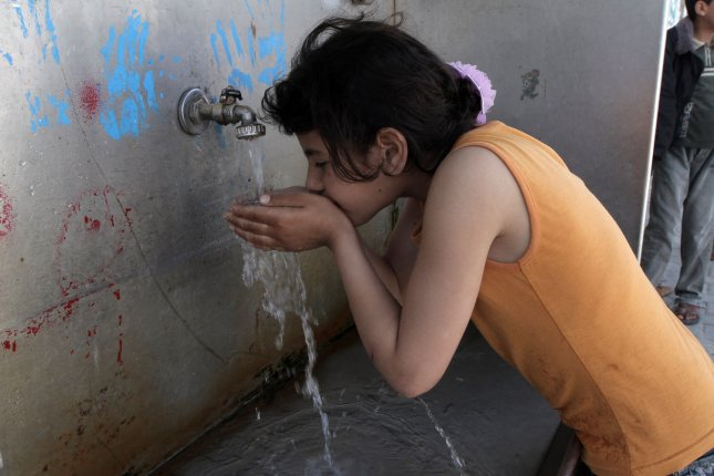 A young child drinks the water from a tap at the United Nations Relief and Works Agency headquarters in the southern Gaza Strip refugee camp of Rafah. File Photo by Ismael Mohamad/UPI