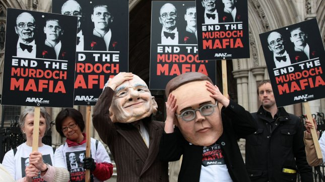 Protesters from the campaign group Avaaz demonstrate outside the High Court with large James and Rupert Murdoch masks in London on Tuesday April 24 2012. UPI/Hugo Philpott