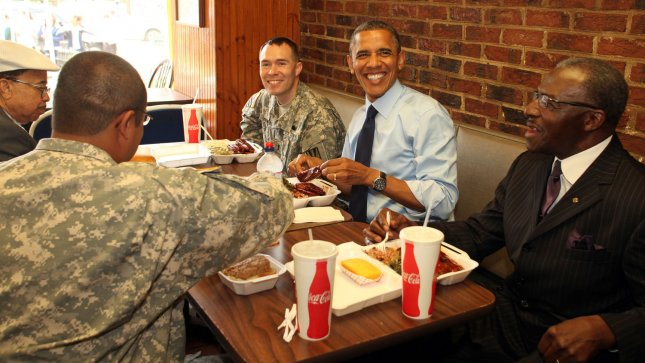 President Barack Obama lunches with two active-duty members of the armed services and two local barbers at Kenny's BBQ on Capitol Hill in celebration of father's day, in Washington, DC on June 13, 2012. Flanking the president are 1st Lieutenant William (Bill) Edwards, left, and barber Otis Big O Gamble. Opposite the president are Nurney Mason of Mason's Barber Shop, left, and Captain Joubert Paulino. UPI/Martin H Simon/Pool