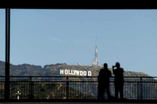 People take photos of the famous Hollywood Sign in Los Angeles in 2013. The sign was altered to read Hollyweed on Sunday morning by who police believe was a lone individual. The change follows numerous other occasions throughout the sign's history in which is was changed to read something different -- including the same thing, Hollyweed, exactly 41 years ago. File Photo by Kevin Dietsch/UPI