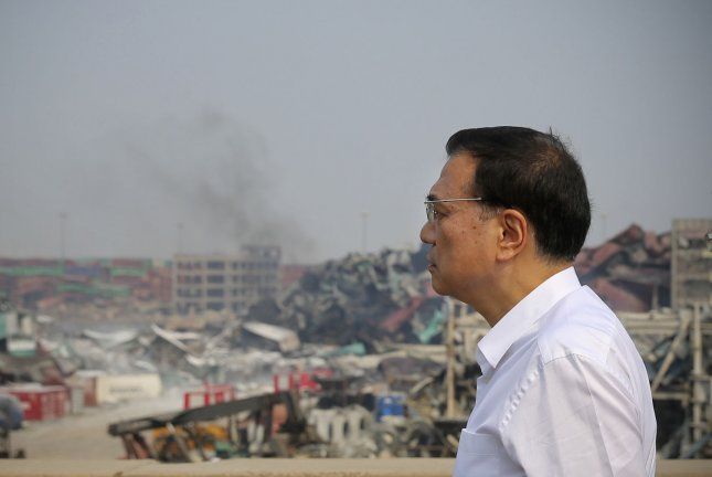 Chinese Premier Li Keqiang inspects the blast area and rescue operations from the roof of a building close to the massive fire and explosion zone caused by hazardous materials stored in a warehouse owned by Ruihai International Logistics in Tianjin on August 17, 2015. File Photo courtesy of Government Handout/UPI
