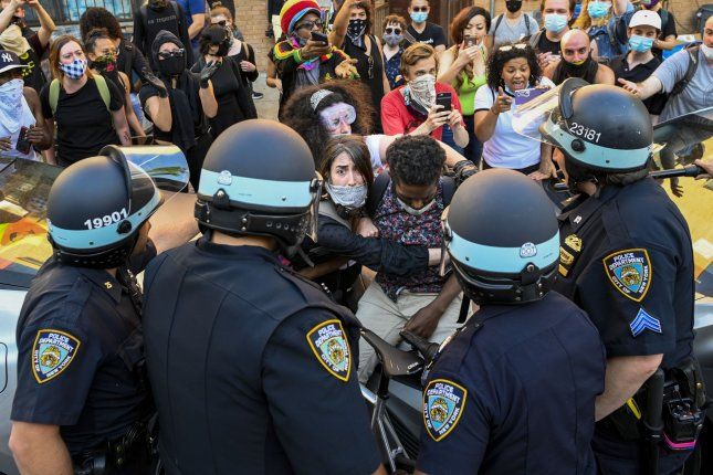A Black Lives Matter protester protects a man from New York Police Department officers as protests around the country continue over the death of George Floyd on May 30, 2020. On Thursday, the New York attorney general accused the NYPD of using excessive force during the summer protests. File Photo by Corey Sipkin/UPI