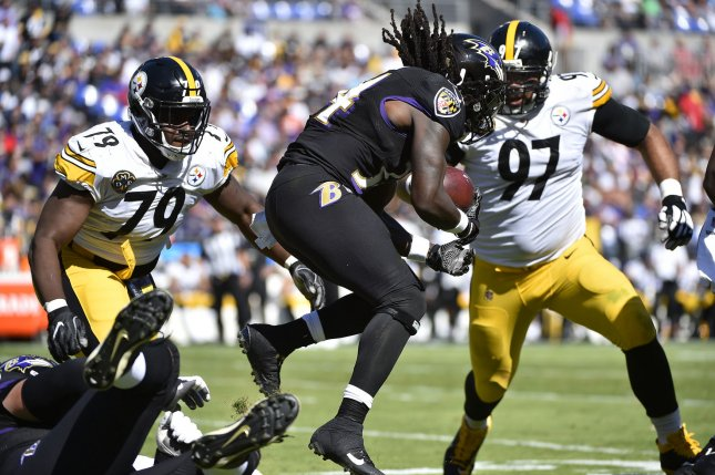 fe7c44433c6 Baltimore Ravens running back Alex Collins (34) drives for extra yardage  against Pittsburgh Steelers defenders Cameron Heyward (97) and Javon  Hargrave (79) ...