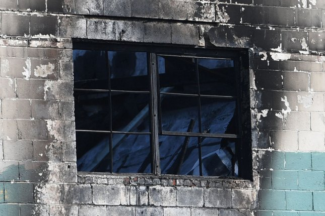 The collasped roof is visible through a window at the scene of a fire at a warehouse known as the Ghost Ship in Oakland, Calif., on December 4, 2016. The jury acquitted one man and was hung on a verdict for a second man, both accused of manslaughter in the case. File Photo by Terry Schmitt/UPI