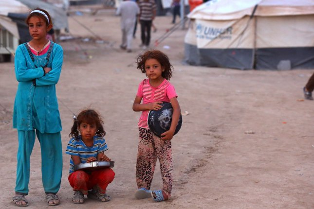 Iraqi refugees girls , who fled from the violence in Mosul, wait to receive food inside the Khazer refugee camp on the outskirts of Arbil, in Iraq's Kurdistan region, June 29, 2014. Tens of thousands of people fled Iraq's second largest city of Mosul after it was overrun by Islamic State militants. Many have been temporarily housed at various IDP camps around the region including the area close to Erbil, as they hope to enter the safety of the nearby Kurdish region. UPI/Ceerwan Aziz