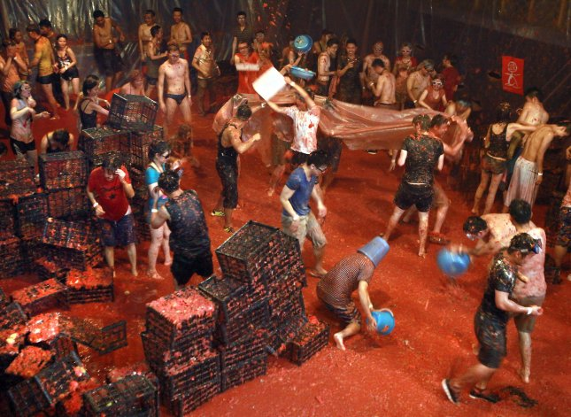 Annual tomato fights, like this one in Beijing in 2014, are being compared to the situation in Nigeria, where a blight has caused a severe tomato shortage. File Photo by Stephen Shaver/UPI