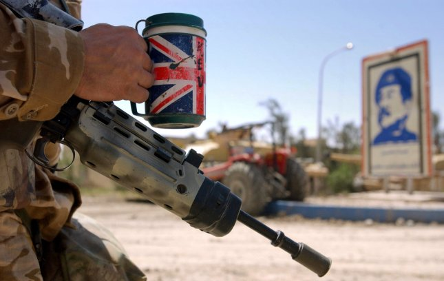 REX2003040321 - IRAQ, April 3 (UPI) -- A soldier serving with Number 1 Company 1st Battalion The Irish Guards, with his mug of tea, resting after a sucessful raid on a large complex on the outskirts if Basra, Iraq, on April 3, 2003. In a dawn raid on a University / factory complex within sight of their patrol base at Bridge Four on the outskirts of Basra the Irish Guards attacked and cleared the base after comming under fire from small arms mortars and SAM Missile systems which were fired from Iraqi positions at a British Lynx Helicopter supporting the Irish Guards. rlw/Giles Penfound/REX FEATURES UPI.**EUROPE OUT**