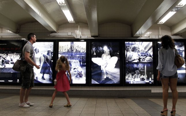 People stop to look at Marilyn Monroe photographs displayed in the New York City subway Aug. 7, 2014. The pictures were taken by Sam Shaw, who photographed many movie stars during his career. UPI/John Angelillo