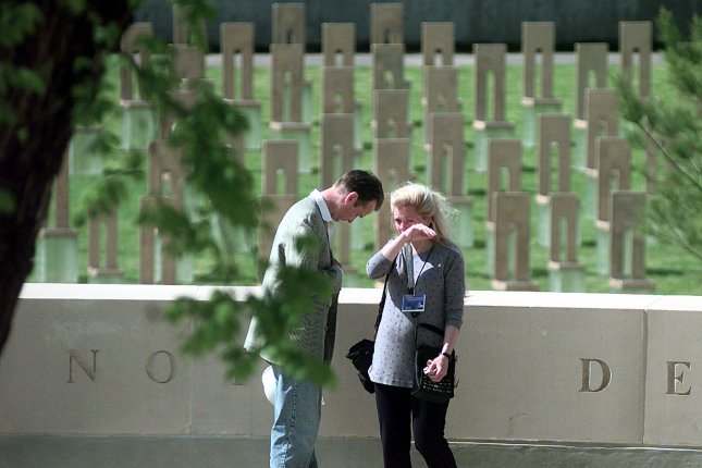 Oklahoma City National Memorial designers Hans and Torrey Butzer share an emotional moment under the survivor tree prior to dedication ceremonies on April 18, 2000. File Photo by bc/Bill Carter/Norman Transcript UPI
