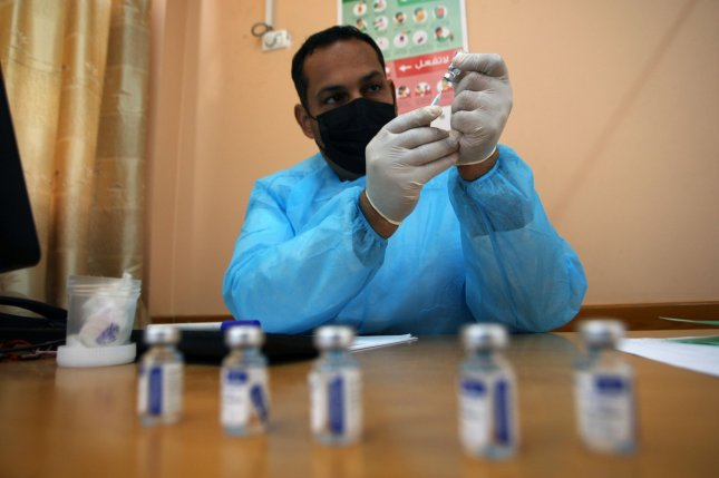 A United Nations Relief and Works Agency for Palestine Refugees worker prepares a shot of Russia's Sputnik V COVID-19 vaccine at a clinic for Palestinian refugees in the southern Gaza Strip on March 3. File Photo by Ismael Mohamad/UPI