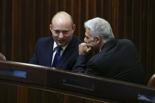 Yamina Party leader Naftali Bennett (L) smiles as he speaks to Yesh Atid Party leader Yair Lapid during a special session of the Knesset where Israeli lawmakers elected Isaac Herzog as the new president in Jerusalem on Wednesday. The two leaders also agreed to form a power-sharing coalition. Pool Photo by Ronen Zvulun/UPI