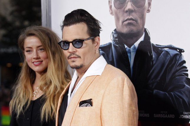 Johnny Depp (R) and wife Amber Heard at a Brookline, Mass., screening of 'Black Mass' on Sept. 15, 2015. The actor recently expressed concern over daughter Lily-Rose Depp's growing fame. File photo by Matthew Healey/UPI