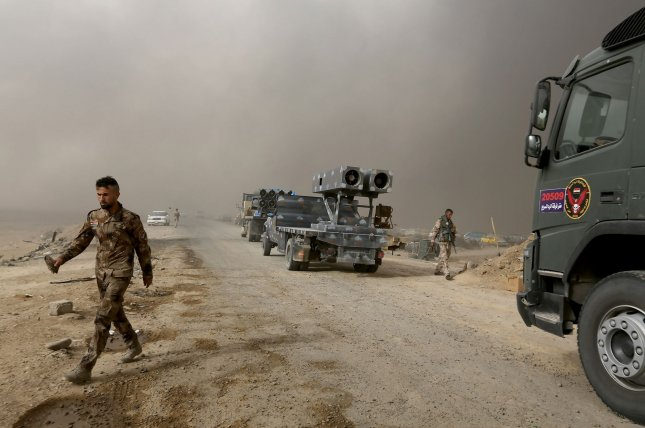 Iraqi army fighters walk around a convoy as smoke rises in the background from burning oil fields damaged during the fighting between Iraqi forces and Islamic State fighters in Qayara in northern Iraq in November. File Photo by Murat Bay/UPI