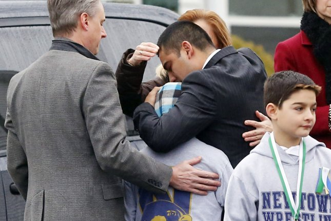 Mourners react in sorrow before the funeral for 6-year-old Jack Pinto at the Honan Funeral Home near Sandy Hook Elementary School in Newtown, Conn. Families of the victims want the state's Supreme Court to reinstate their lawsuit against Remington Outdoor Co. File Photo by John Angelillo/UPI