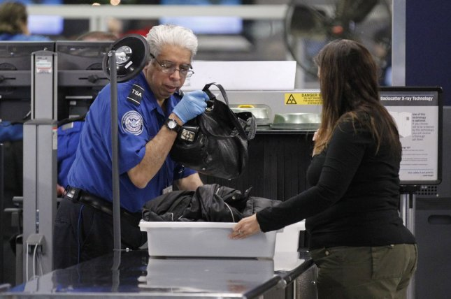 A TSA screener helps a passenger at a security checkpoint at O'Hare International Airport on November 24, 2010 in Chicago. Last week, TSA said it confiscated a record number of guns during 2017. File Photo by Brian Kersey/UPI